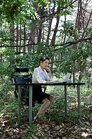 Business woman looking at laptop on desk in forest