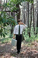 Businessman holding briefcase standing in forest