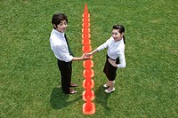 businessman and woman shaking hands with traffic cones