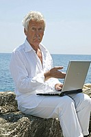 man senior with notebook at sea side