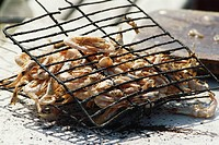 Shrimp being grilled in grid iron