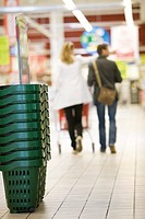 Stack of shopping baskets, shoppers in background (thumbnail)