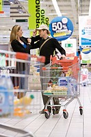 Couple in supermarket, man trying on hat