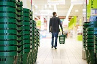 Shopping baskets stacked in rows, shopper in background (thumbnail)
