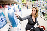 Woman selecting bottle of detergent from supermarket shelf