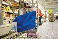 Reusable shopping bag hanging from shopping cart in supermarket