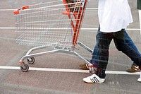 Empty shopping cart being pushed across parking lot