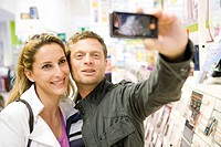 Couple taking self portrait with demo photophone in store
