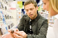 Couple shopping together, man showing cell phone to woman