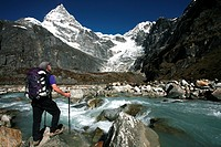 A trekker pauses for a break on the edge of a glacial stream on the way to Mera Peak, a popular trekking peak in the Khumbu Region, near Mount Everest...