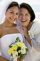 Bride and mother with flowers smiling close_up portrait