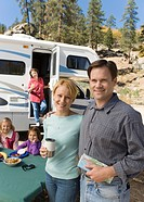 Couple and family outside RV in campground