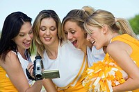 Cheerleaders watching video on video camera