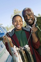 Middle_aged man with grandson holding fishes smiling portrait
