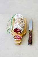 Hard cured sausage with nuts on a wooden board with knife