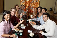 Young people toasting with saki cups in Japanese restaurant