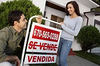 Couple standing in front of house with Sold sign portrait
