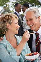 Cheerful elegant couple sharing dessert together at garden party