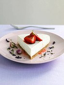 Piece of cheesecake with strawberries and lavender flowers