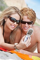 Young couple lying on beach using cell phone