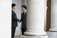 Two business men shaking hands outside building by pillar