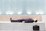 Businessman lying on concrete bench side view