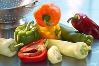 Assorted peppers beside colander