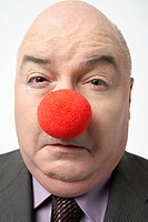 Bald businessman Wearing Clown Nose frowning close_up