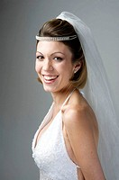Bride in her 20s smiles at the camera in a studio setting