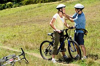 Couple with bicycles in countryside, man adjusting woman´s helmet