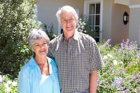 Mature couple arm in arm outside house, smiling, portrait (thumbnail)