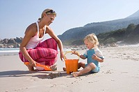 Mother and daughter 1-3 with bucket and spade on beach (thumbnail)