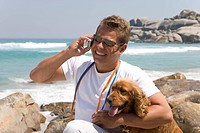 Man embracing dog on beach, using mobile phone, smiling