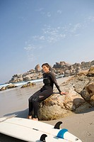 Woman surfer in wetsuit with surfboard on rock on beach, smiling