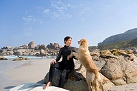 Female surfer in wetsuit with dog on beach