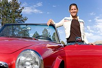 Woman standing next to red convertible