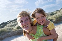 Portrait of mother piggybacking daughter (thumbnail)