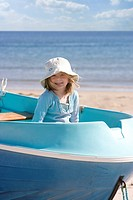 Portrait of girl sitting in rowing boat on beach