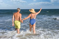 Senior couple walking in sea, rear view