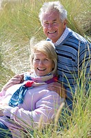 Portrait of senior couple sitting on beach