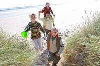 Parents with children running on beach