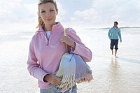 Young woman walking on beach, man in background