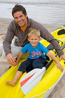 Portrait of father and son with kayak on beach