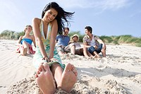 Portrait of young Asian woman sitting at beach, friends in background