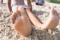 Close-up of woman's barefeet in sand at beach (thumbnail)