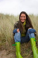 Portrait of young woman in boots sitting in grass