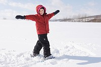 Young girl standing in snow with arms outstretched, Stayner, Ontario