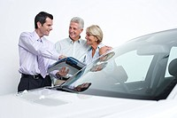 Car salesman talking to couple about new car