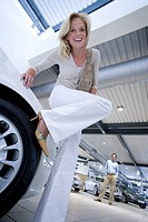 Woman in high heels leaning on new car