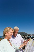 Couple looking at map on coastal highway